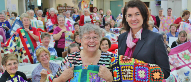 Woombye Community Bank Branch Manager visits a group crocheting blankets for those in need.