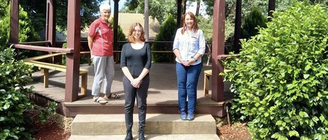 Two female Directors and a female scholarship recipient standing on steps in a park