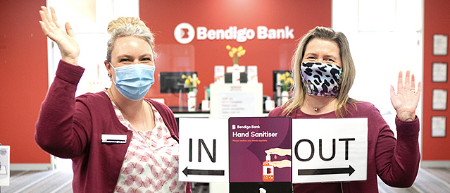 Two Mt Eliza staff members standing at the branch entrance hand sanitiser station wearing masks and waving. Signs on the sanitation station say In and Out.