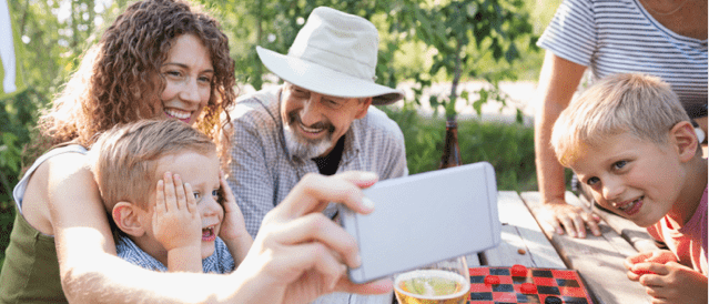 Family sitting at table looking at mobile