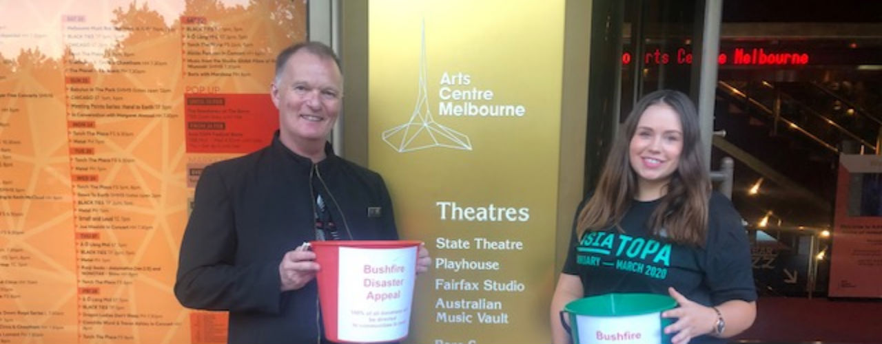 Two Arts Centre staff holding fundraising buckets outside the Arts Centre in Melbourne.