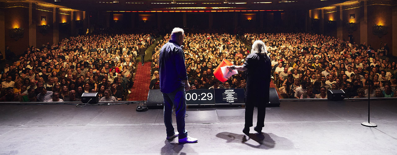 View from back of stage to audience - Denise Scott, holding a collection bucket, and Peter Helliar are on stage in front of a full house.