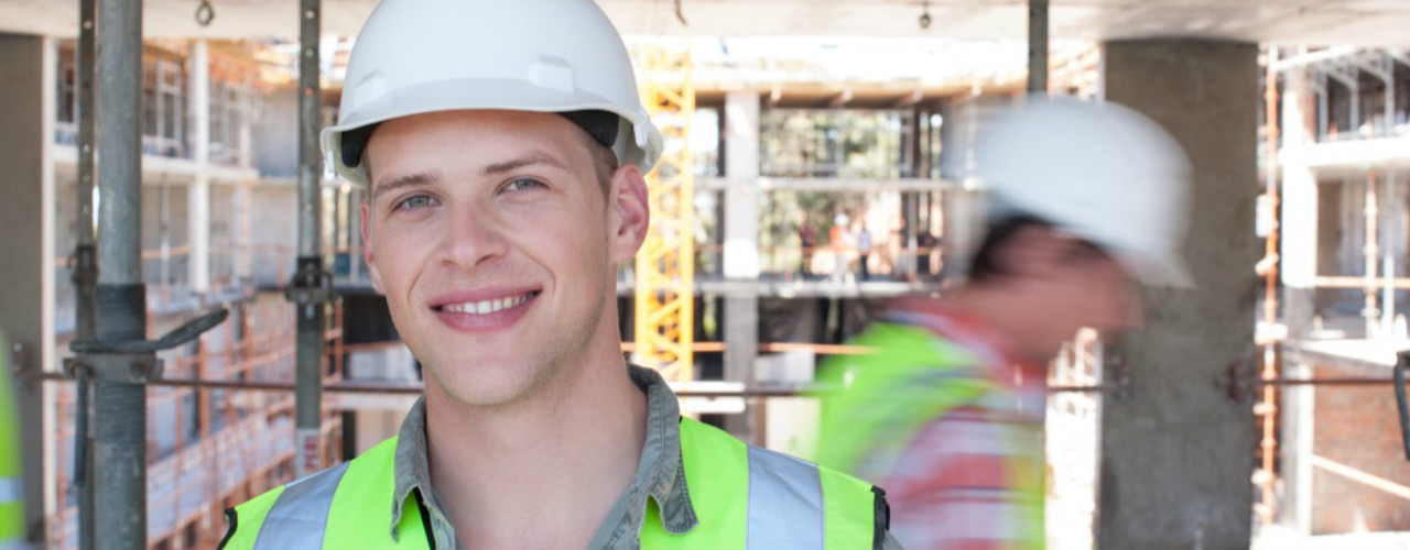 Young man in hardhat and safety vest on building site.