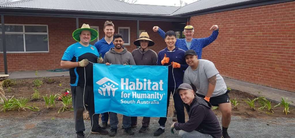 Volunteers standing in front of newly planted garden holding a Habitat for Humanity South Australia banner.