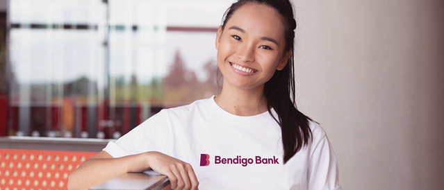 Young woman leaning on rail wearing a tshirt with the bank's new brand logo.