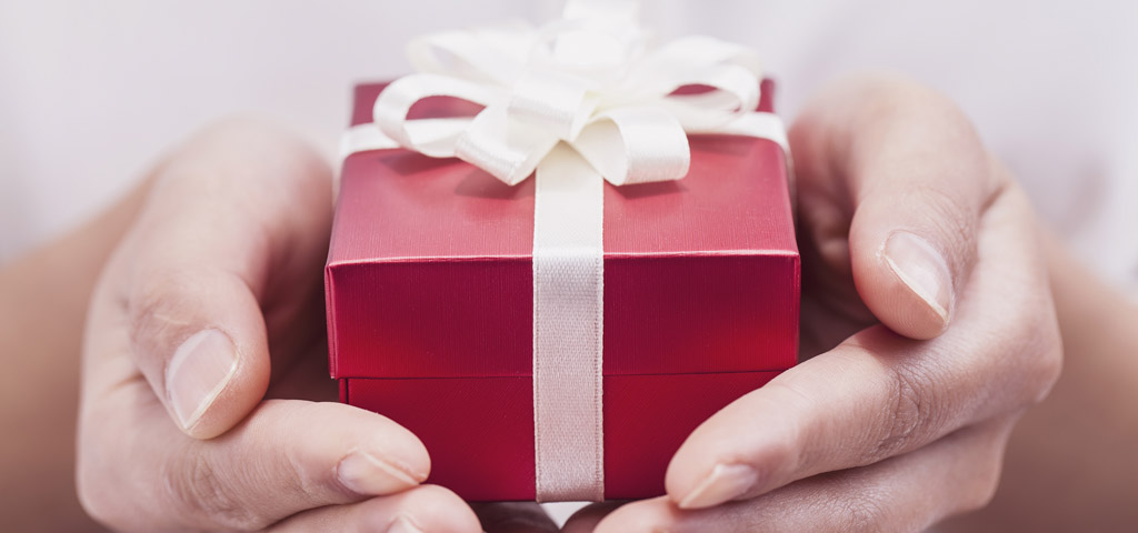 Hands holding a red gift box with white ribbons.
