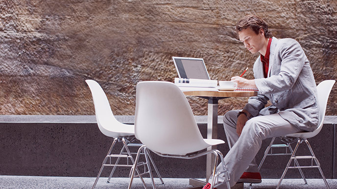 Man researching on his laptop at an outdoor cafe table.