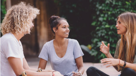 Two females and a male sitting down in a circle, talking to each other smiling