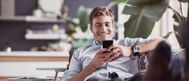 Man sitting on couch looking at mobile phone