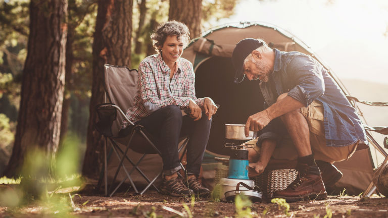 older couple camping standing in front of a tent about to cook on their portable butane cooker