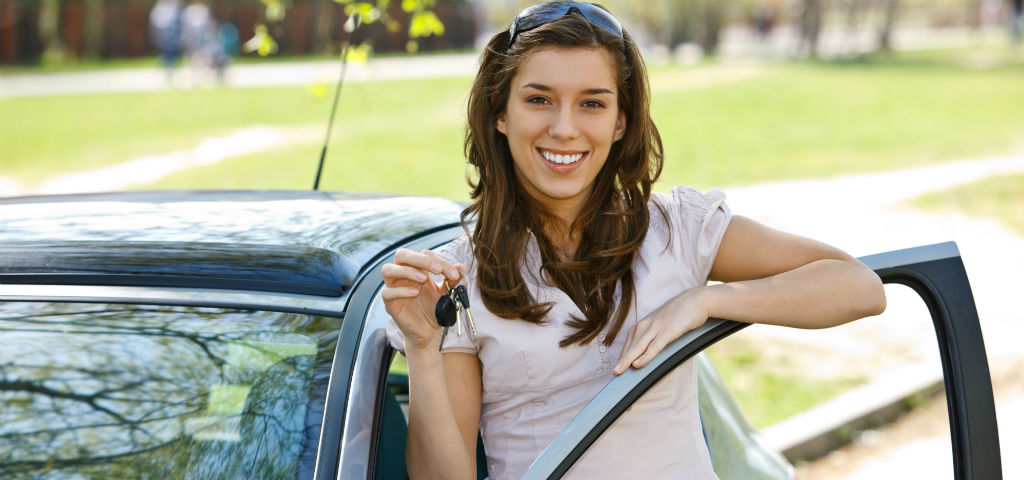 Young smiling female standing next to a car holding car keys up