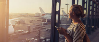 Woman in airport looking out over planes parked at terminal.
