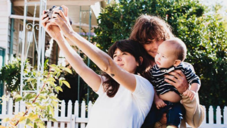 woman taking a selfie if her partner and baby boy in front of their house