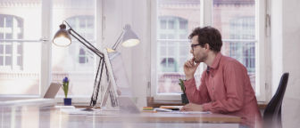 Man sitting at desk looking at his computer screen.